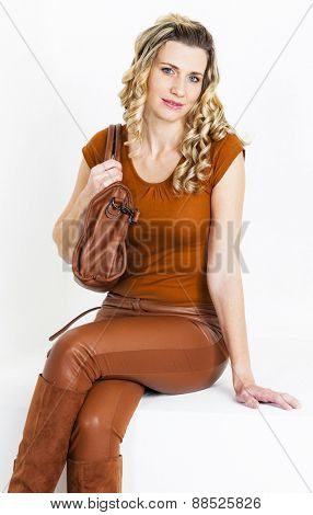 portrait of sitting woman wearing brown clothes and boots with a handbag