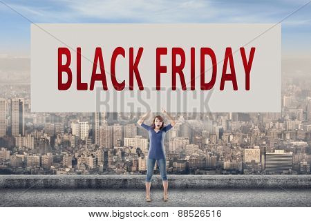Black Friday, words on blank board hold by a young girl in the outdoor.