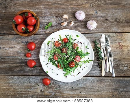Salad with arugula, cherry tomatoes, sunflower seeds and herbs on white ceramic plate over rustic wo