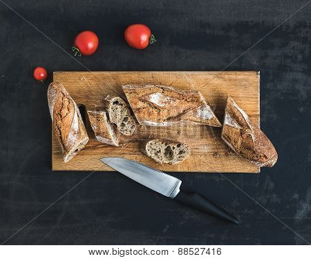 French baguette cut into pieces and cherry-tomatoes on a rustic wooden board