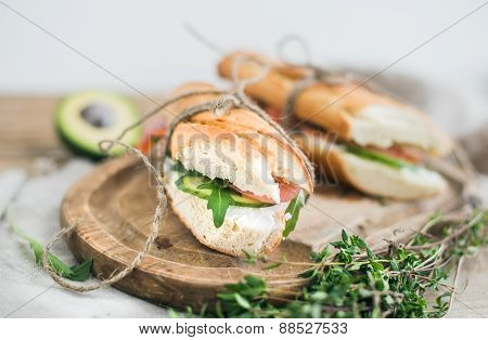 Salmon, avocado and thyme sandwiches in baguette tied up with decoration rope on a rustic wooden boa