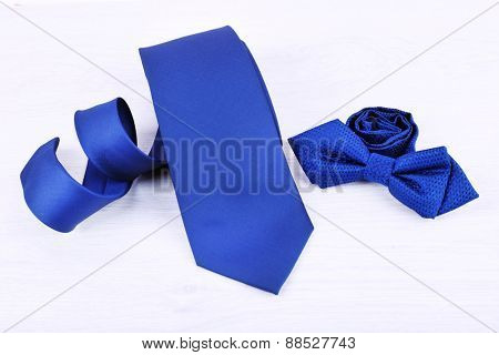 Male necktie and bow tie on wooden table background