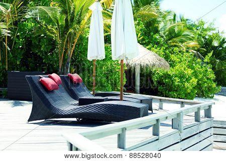 Sunbed in resort in hotel room over blue ocean in Baros Maldives