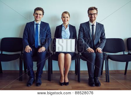 Happy co-workers sitting on chairs along wall