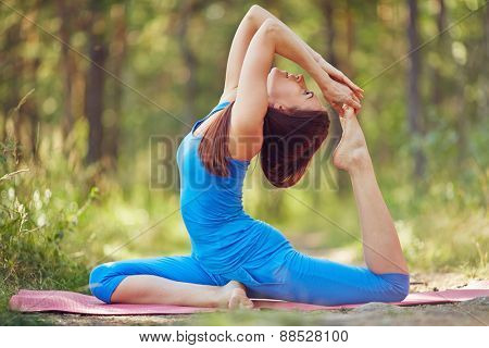 Active woman doing stretching exercise outdoors