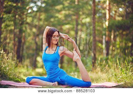 Flexible girl doing yoga exercise outdoors