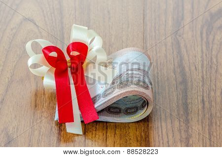 Roll Of Thai Baht On Wood Background