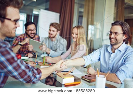Businessmen handshaking on background of working team
