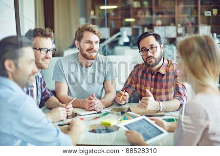 Group of confident managers listening to female employee