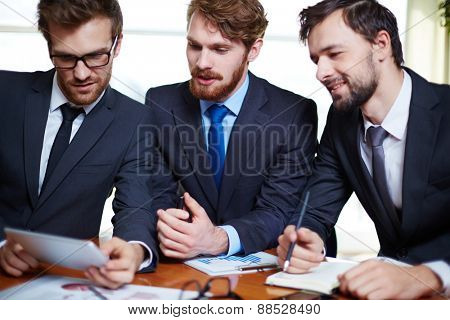 Group of managers discussing electronic document or data in touchpad