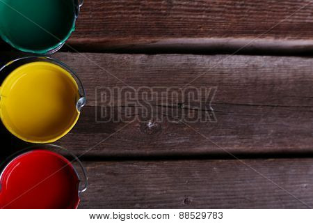 Metal buckets with colorful paint on wooden background