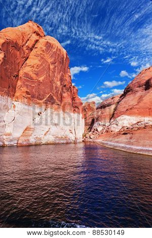 Lake Powell is surrounded by magnificent red hills. Walk on the boat at sunset. Scenic huge artificial water basin of the Colorado River, USA
