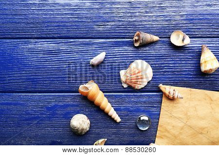 Card blank with shells on wooden background