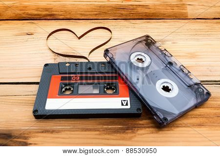 Vintage Audio Cassette With Loose Tape Shaping Two Hearts On A Wooden Background.