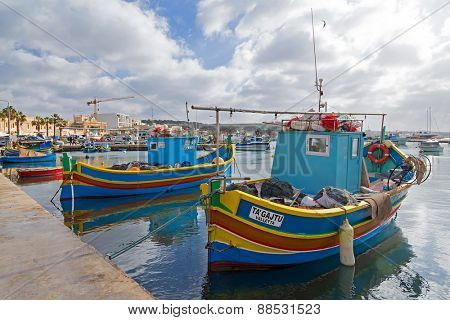 MARSAXLOKK, MALTA - JANUARY 11, 2015: Luzzus, traditional fishing boats in the harbour.