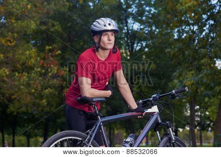 Sport Concept: Portrait Of Young Thinking  Caucasian Handsome Athlete Standing With Bike Outdoors