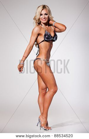 Smiling athletic woman in black bikini showing muscles on grey background