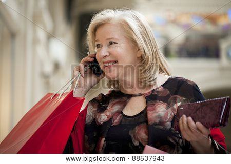 Mature happy blonde woman with shopping bags, calling by phone
