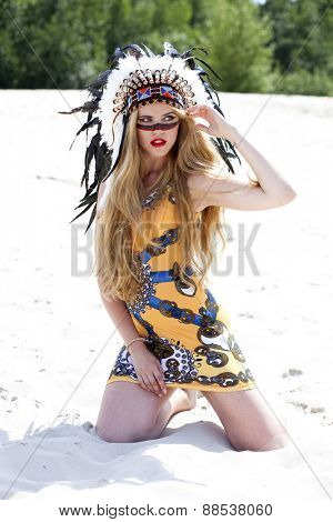 Young blonde woman in costume of American Indian sits on the sand