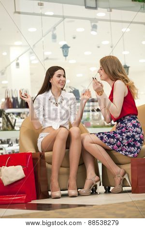 Two young girl friends sitting in the shop and relax after shopping