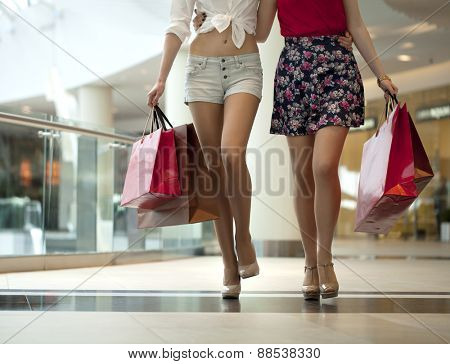 Two pairs of female legs with shopping bags in their hands