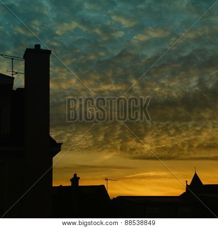 Blue and yellow sunset on a silhouette of a houses rooftop  in Europe