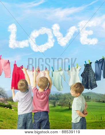 Happy little boys hanging laundry on countryside