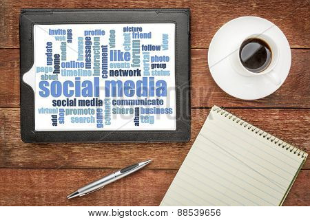 social media word cloud on digital tablet - top view on a rustic barn table with coffee and notepad