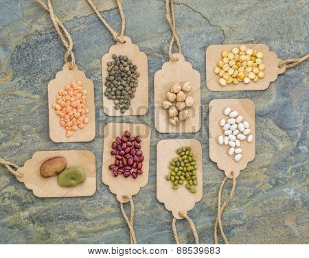legume abstract (fava bean, red lentils, adzuki bean, soy, mung bean,navy bean, yellow pea, French lentils) - top view of paper price tags against slate stone