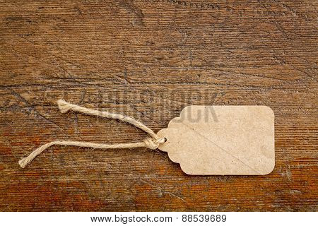 blank paper price tag with a twine against a rustic wood