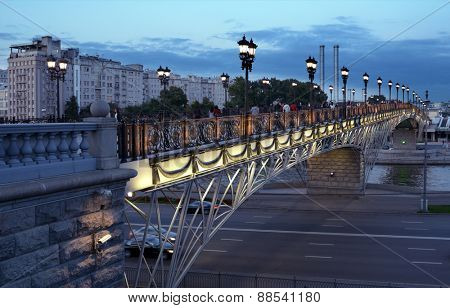 MOSCOW, RUSSIA - JULY 28, 2013: People strolling on the Patriarch bridge in evening. Patriarch bridge was built in 2004, and now it's the lovely place for walks