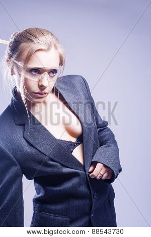 Fashion Concept: Shaped Body Of Young Caucasian Sexy Blond Model Posing In Gray Suite Against Gray B