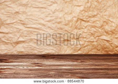 Crumpled paper background and wooden table surface.