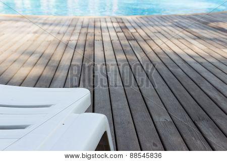 White Plastic Sunbed Beside Swimming Pool