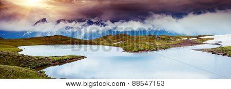 Fantastic landscape with lake Koruldi and overcast sky at the foot of  Mt. Ushba. Upper Svaneti, Mestia, Georgia, Europe. Caucasus mountains. Beauty world.