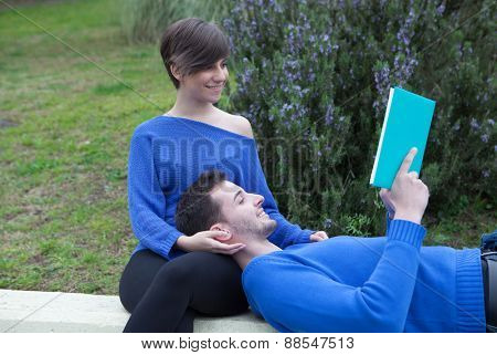 Young pretty couple together reading a book together on the grass