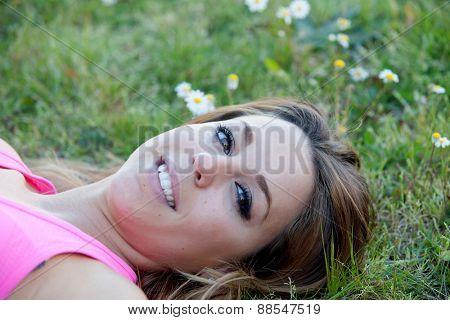 Pretty blonde woman lying in a beautiful field full of flowers