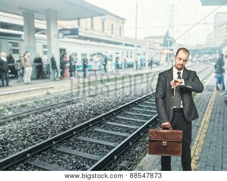 standing businessman at train station