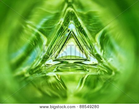 Abstract inside triangle glass bottle emerald green background
