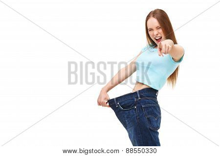 You Can Do It! Young Slim Woman With Large Jeans Pointing Finger At You - Isolated On White.