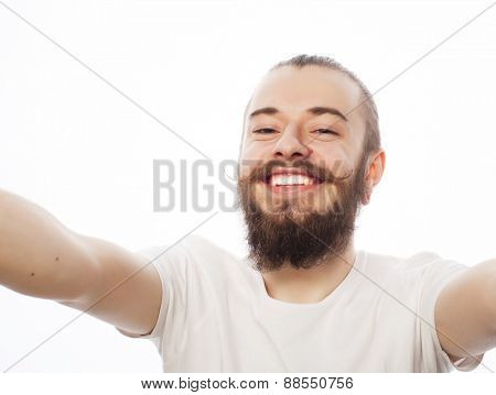 Tehnology concept: Happy selfie. Handsome young man  holding camera and making selfie and smiling.