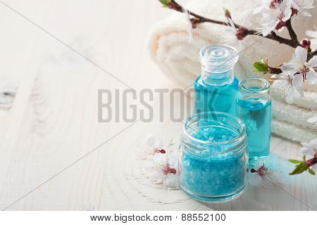 Mineral bath salts,  shower gel, towels  and flowers on the  wooden table. Shallow DOF. Focus on the salt.