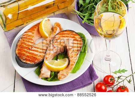 Grilled salmon, salad and white wine on wooden table