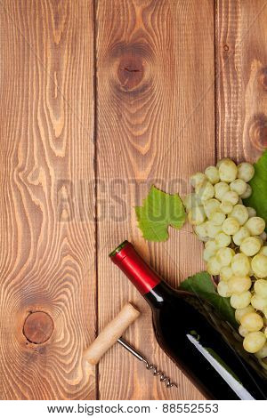 Red wine bottle and bunch of white grapes on wooden table background with copy space