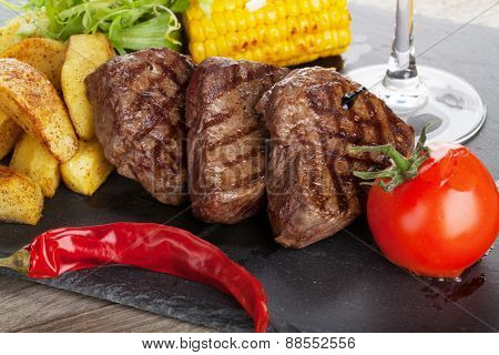 Steak with grilled potato, corn, salad and red wine closeup