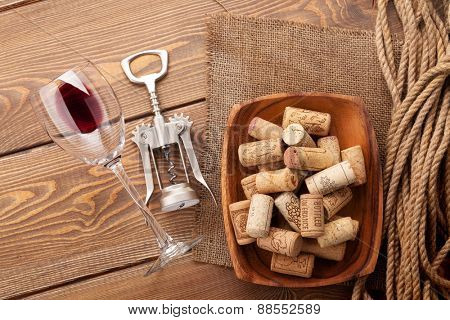 Red wine glass, corkscrew and bowl with corks over rustic wooden table background. Top view