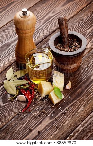 Various spices and condiments on wooden background