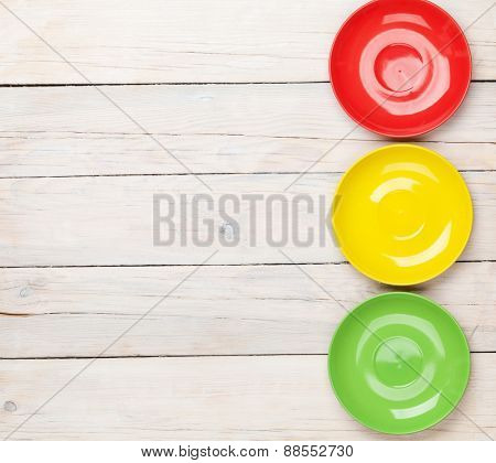 Colorful plates over white wooden table background with copy space