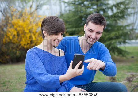 Lovers in the park dressed in blue looking the mobile phone