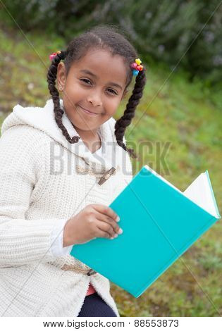 Pretty african girl with winter clothes in the park reading a book